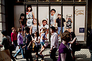 Crowds of shoppers pas an advert for GAP kids in central London. Shops in the heart of London's mid range shopping district on Regent Street. This is the busiest area for mainly fashion retail in the capital.
