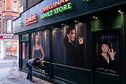 Cleanerwiping down the new exterior to Sohos Original Adult Store in Soho on 1st December 2020 in London, United Kingdom. Traditionally, this area of the West End has been the centre of the adult entertainment industry in London, UK with shops selling adult industry goods like this landmark shop.