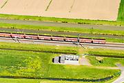 Nederland, Gelderland, Gemeente Zaltbommel, 23-08-2016; Rijksweg A15 ten westen van knooppunt Deil . Parallel aan de snelweg de Betuweroute met goederentrein (kolen en/of erts), richting haven van Rotterdam. AT-station voor stroomvoorziening van de spoorlijn (25kV). AT=autotransformatorsysteem.<br /> Main motorway A15 (Rotterdam Harbour - Germany) with Betuweroute, freight railway w coal train <br /> <br /> aerial photo (additional fee required); luchtfoto (toeslag op standard tarieven); copyright foto/photo Siebe Swart