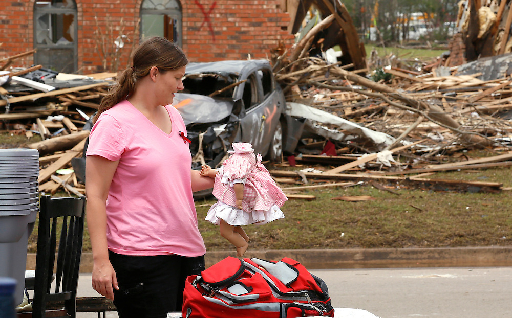 Tracy Stephan holds one of daughters dolls with a missing head at her tornado-destroyed home on 6th Avenue in Moore, Oklahoma May 23, 2013. The tornado was the strongest in the United States in nearly two years and cut a path of destruction 17 miles long and 1.3 miles wide. REUTERS/Rick Wilking (UNITED STATES)