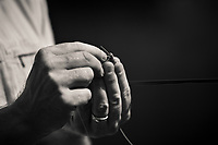 close up black and white of male anger's hands while tying on a fly