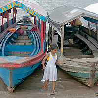A young girl fetches water from the between boats pulled ashore on the Amazon River at Iquitos, Peru.
