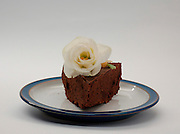 Birthday cake, a slice of chocolate cake, with a white Marzipan rose as decoration