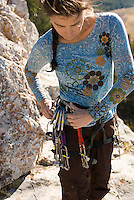 A young woman attaches gear to her harness while rock climbing in Grand Teton National Park, Jackson Hole, Wyoming.
