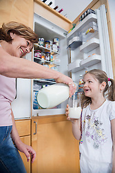 Grandmother pouring milk into glass for granddaughter