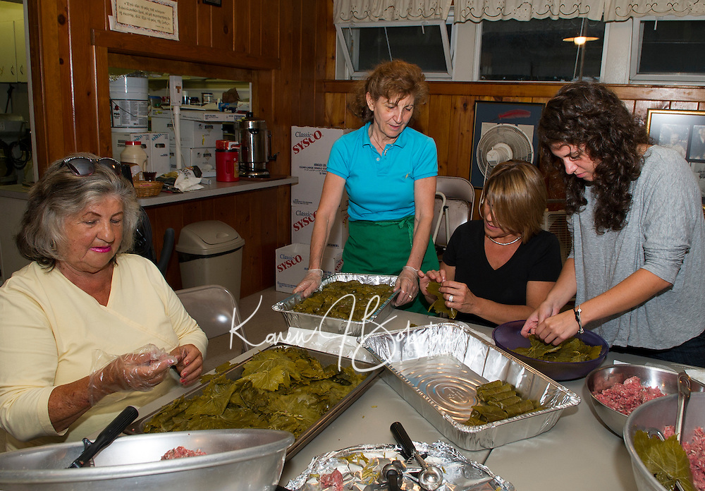 """Angie Argiropolis, Bessie Kafanelis and Christine and Samantha Kemos prepare """"Dolmathes"""" (stuffed grape leaves) in preparation of the 26th annual Greek Summer Festival at Taxiarchai Greek Orthodox Church in Laconia on Saturday starting at 10am.  (Karen Bobotas/for the Laconia Daily Sun)"""