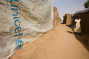 A young girl walks past UNICEF-supplied sheeting used to cover a makeshift roof lining of a home in the 4 sq km Abu Shouk refugee camp which is (disputedly) home to 38,000 displaced persons and families on the outskirts of the front-line town of Al Fasher (also spelled, Al-Fashir) in north Darfur. .