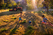Two boys happily playing unaccompanied outside in field the late sunshine 14th July 2019 in the French village of Lagrasse, France. One is playing with a football, the othe using a hula hoop.