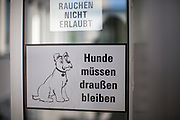 "Two sign reading""Dogs have to stay outside"" and ""Smoking not allowed"" at a health insurance building in Germany."