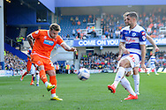 Blackpool's David Goodwillie crossing the ball past Queens Park Rangers Aaron Hughes. Skybet football league championship match , Queens Park Rangers v Blackpool at Loftus Road in London  on Saturday 29th March 2014.<br /> pic by John Fletcher, Andrew Orchard sports photography.