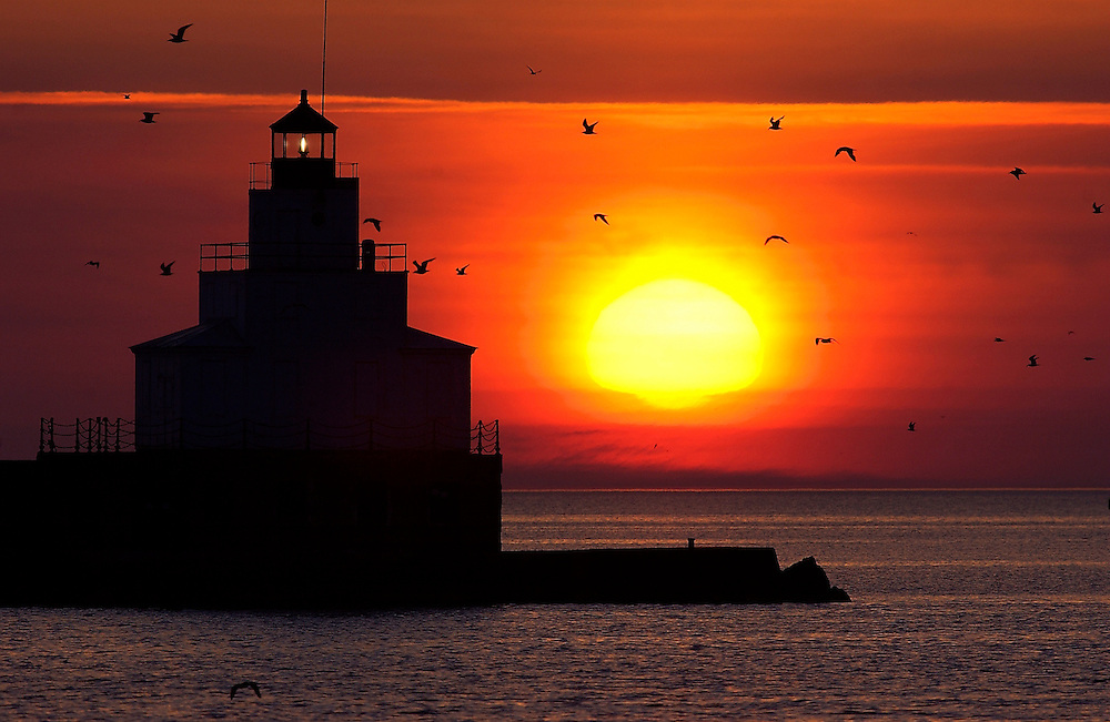 The sun rises over Lake Michigan as sea gulls fly around the lighthouse in Kewaunee, WI on Monday May 12, 2003.