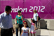 Area around Stratford in East London, home to the 2012 Olympic Games. Aa an event goes on behind the London 2012 sign, people try to peer through to look.