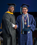Dameion Crook presents Valdictorian Kevin Villalta with the first diploma during the first ever graduation for Mickey Leland College Preparatory Academy, May 27, 2015.