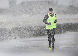 © Licensed to London News Pictures. 08/02/2019. Southsea, UK. A jogger runs along the sea front at Southsea, near Portsmouth, as waves hit the sea wall. Storm Erik is hitting southern parts of the UK. Photo credit: Peter Macdiarmid/LNP