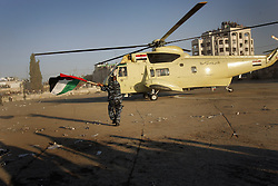 A Palestinian soldier runs with a flag towards one of the Egyptian military helicopters that delivered Yasser Arafat's body for the funeral at his compound, Ramallah, Palestinian Territories, Nov. 12, 2004. Arafat died in a Paris hospital at the age of 75.