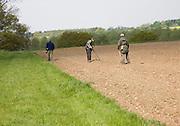 Three men using metal detectors in a field, Rendlesham, Suffolk, England