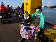 22 JANUARY 2019 - PHRA PRADAENG, SAMUT PRAKAN, THAILAND:  A woman with her bicycle on a motorcycle and vehicle ferry crossing the Chao Phraya River in Phra Pradaeng. The use of vehicle ferries across the river has gone down as the government has built bridges to connect communities on both sides of the river. The Phra Pradaeng ferries are the busiest vehicle ferries in the Bangkok metropolitan area. Since the BTS Skytrain now comes close to the ferry, the number of commuters going into Bangkok that use the ferry has increased.   PHOTO BY JACK KURTZ