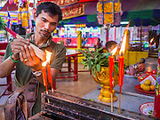 18 JANUARY 2015 - BANGKOK, THAILAND: A man lights incense as an offering at the Chaomae Thapthim Shrine, a Chinese shrine in a working class neighborhood of Bangkok near the Chulalongkorn University campus. The Sai Yong Hong Opera Troupe's nine night performance at the shrine is an annual tradition and is the start of the Lunar New Year celebrations in the neighborhood. The performance is the shrine's way of thanking the Gods for making the year that is ending a successful one. Lunar New Year, also called Chinese New Year, is officially February 19 this year. Teochew opera is a form of Chinese opera that is popular in Thailand and Malaysia.             PHOTO BY JACK KURTZ