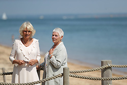 July 25, 2018 - Cowes, United Kingdom - Image licensed to i-Images Picture Agency. 24/07/2018. Cowes, United Kingdom. The Duchess of Cornwall is welcomed by Dame Judi Dench as she arrives at Queen Victoria's private beach, next to the monarch's holiday home in East Cowes on the Isle of Wight,  United Kingdom. (Credit Image: © Pool/i-Images via ZUMA Press)