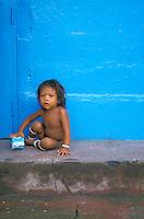 Niño aborigen sentado en acera, Puerto Ayacucho, Amazonas, Venezuela.