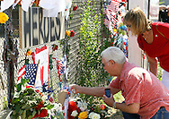People look at momentos left at a memorial in Prescott, Arizona to firefighters killed in the nearby wildfire July 2, 2013.   An elite squad of 19 Arizona firemen was  killed in the worst U.S. wildland firefighting tragedy in 80 years apparently outflanked and engulfed by wind-whipped flames in seconds, before some could scramble into cocoon-like personal shelters on June 30, 2013. Beyea was a friend at school with Ashcraft. REUTERS/Rick Wilking (UNITED STATES)