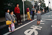 Maya Ukita (left) and her mother, Sayo (red shirt) watch a neighbor boy jump rope while waiting for the bus to pick up the kids in the morning for their kindergarten class. Bus stop in Kodaira City, Japan. Material World Project. The Ukita family lives in a 1421 square foot wooden frame house in a suburb northwest of Tokyo called Kodaira City.