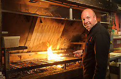 """MALDEGEM, BELGIUM - JUNE-18-2011 - Peter De Clercq, Grill Master, TV host, and the 2003 World BBQ Champion, designed and built his grill from scratch, installing a large metal hopper at the back of the grill, where whole oak, birch, apple, and cherry logs are burned to embers, which fall down a chute under the grill grates. """"Charcoal has the taste burned out of it,"""" De Clercq says. """"You can't beat the flavor of wood."""" (Photo © Jock Fistick)"""