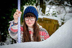 Seonaid Wilson from Biggar, South Lanarkshire measures the depth of snow on a car.  Almost nine inches (22.5cm) of snow has fallen in the past 24 hours with more forecast.<br /> <br /> (c) Andrew Wilson | Edinburgh Elite media