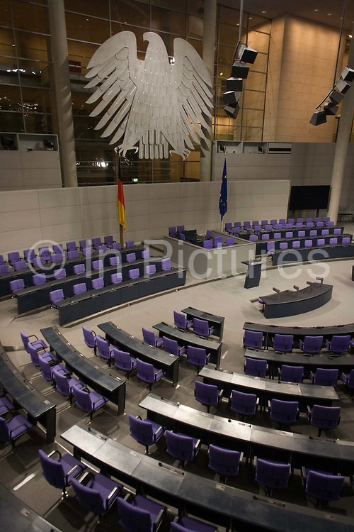 The Plenary Chamber in the centre of the old Reichstag building in central Berlin, Germany. The Bundestag is a legislative body in Germany. The new Reichstag building was officially opened on 19 April 1999. At least 598 Members of the Bundestag are elected and meet here.  The Reichstag is the seat of the political centre of Germany. The parliament holds its meetings at the plenary chamber underneath the amazing dome of glass and steel. The ramps which lead you elliptical to the top of the dome make a great visual impact. More than 800 tons weighs the cupola of the Reichstag. The building outlay amounts to a considerable sum of 600 million Deutsche Marks. The directive architect was Sir Norman Foster.