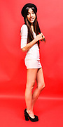 Young stylish 18 year old female teen happy and cheeky on red background