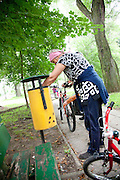 Polish woman attendant age 55 removing trash from garbage can receptacle in city park. Paderewski Park Rzeczyca Central Poland