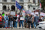 April 20, 2020 -- Protesters hold signs and flags in front of the Pennsylvania State Capitol during a protest to demand that Governor Tom Wolf allow businesses to reopen during the COVID-19 pandemic.
