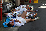 Mikoshi supporters sleep on the street on the third day of the Sanja matsuri, Asakusa, Tokyo, Japan. Sunday May 21st 2017. The Sanja matsuri (Three shrines festival) is one of the biggest Shinto festivals in Japan. It takes place for 3 days around the third weekend of May and features over 100 large and small mikoshi, or portable shrines, which are paraded around the streets of the historic Asakusa district in Tokyo. to bring blessings and good luck on the inhabitants. The events attracts up to 2 million visitors each year.