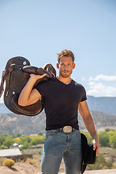 Good looking rugged cowboy with a saddle on a ranch