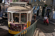 As a scooter rider on a Vespa edges past, a number 28 tram rumbles along a narrow street in the Portuguese capital, on 13th July 2016, in Lisbon, Portugal. The 28 is one of the trams not only used by the people of the capital but also of an increasing number of tourists who ride the entire route from Prazeres cemetery in the west of the city, to Rossio in the centre, after a loop through some of the most amazing streets and landmarks. So crowded is the 28, that older locals often can't sit down, having to stand over younger, inconsiderate tourist families who want a window seat for the entire journey - and back. Notices at termini remind visitors that this is a public service and to consider locals. (Photo by Richard Baker / In Pictures via Getty Images)