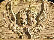 Two angel faces and wings on stone gravestone in church graveyard, Suffolk, England, UK