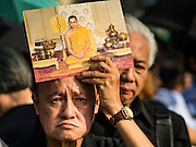 14 OCTOBER 2016 - BANGKOK, THAILAND: A man holds a portrait of the King while he stands in line to enter the Grand Palace in Bangkok to pay respects to Bhumibol Adulyadej, the King of Thailand, who died Oct. 13, 2016. He was 88. His death comes after a period of failing health. With the king's death, the world's longest-reigning monarch is Queen Elizabeth II, who ascended to the British throne in 1952. Bhumibol Adulyadej, was born in Cambridge, MA, on 5 December 1927. He was the ninth monarch of Thailand from the Chakri Dynasty and is known as Rama IX. He became King on June 9, 1946 and served as King of Thailand for 70 years, 126 days. He was, at the time of his death, the world's longest-serving head of state and the longest-reigning monarch in Thai history.     PHOTO BY JACK KURTZ