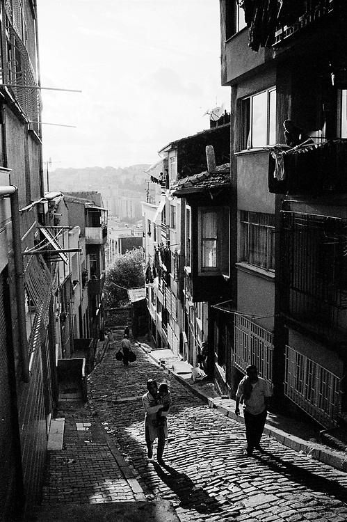 A family walks up the hill in a poorer section in Sahkulu neighborhood in Beyoglu, Istanbul.