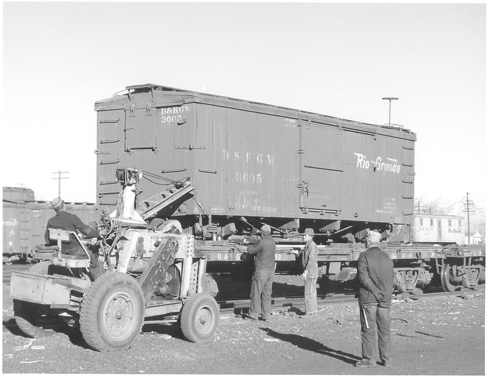 3/4 view of box car #3605 on standard gauge flat car.  Yard tractor/crane is assisting with chore.<br /> D&RGW  Alamosa, CO  Taken by Richardson, Robert W. - 12/14/1955
