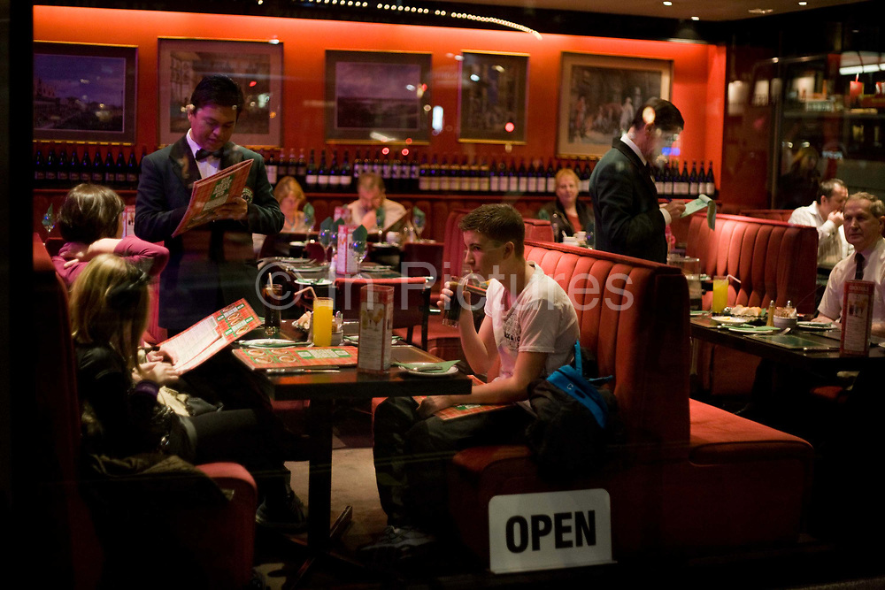Seen through the window of a generic central London restaurant, we see a family, possibly tourists, seated in full view of the street's passers-by, while ordering their dinners from a waiter. The man is standing over them, writing down a mother's orders while at the next row of seats, a man is also telling his own waiter what his dinner will be. An Open sign has been placed to attract more trade into this business, a favourite among tourists visiting Theatreland in the capital's West End. It is early evening and the background street is dark with other businesses illuminated. Other couples and customers are also sitting at tables waiting for their food to arrive and in the foreground, a young man sips a glass of Coke from a straw.