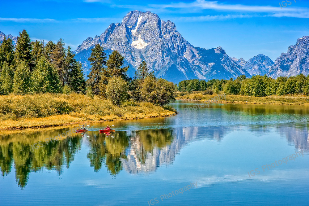Kayaking around Oxbow bend on the snake river against the backdrop Mount Moran and the Teton Range