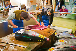 highly skilled wholesale workers, carefully filleting raw bluefin tunas with specially designed Japanese tuna knives, Thunnus sp., Tsukiji Fish Market or Tokyo Metropolitan Central Wholesale Market, the world's largest fish market, hadling over 2,500 tons and over 400 different kind of fresh sea food per day