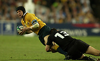 Photo: Richard Lane.<br />New Zealand v Australia. Semi-Final, at the Telstra Stadium, Sydney. RWC 2003. 15/11/2003. <br />Stephen Larkham is brought down by Leon MacDonald.