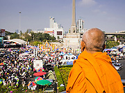 19 JANUARY 2014 - BANGKOK, THAILAND:  A Buddhist monk looks at scene at Victory Monument after unknown assailants threw grenades at anti-government protestors. Twenty-eight people were injured in the blasts. Hundreds of people came to Benjasiri Park, a few hundred meters from the anti-government protest site in Asok Intersection, Sunday evening to pray for peace and rally for a respect for democracy Sunday. The vigil took place a few hours after a two explosive devices, thought to be grenades, were thrown at the protest site near Victory Monument, several kilometers north of Asok. The grenade attack Sunday was the 2nd daytime grenade attack in three days on anti-government protestors. No arrests have been made in the incidents.   PHOTO BY JACK KURTZ