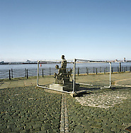 A fenced off statue of an immigrant family at the Pier Head on the Mersey waterfront in Liverpool during regeneration work in preparation for the city's status as 2008 European Capital of Culture. The Mersey is a river in north west England which stretches for 70 miles (112 km) from Stockport, Greater Manchester, ending at Liverpool Bay, Merseyside. For centuries, it formed part of the ancient county divide between Lancashire and Cheshire.