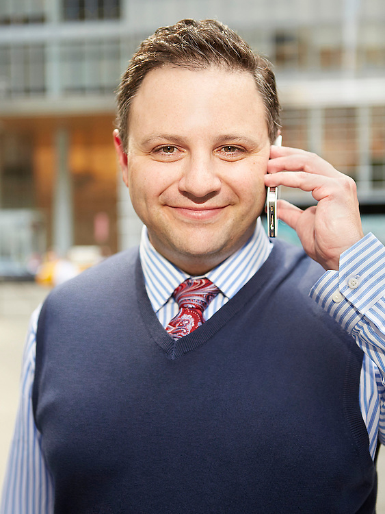 Portrait photograph of beaming businessman with cellphone in NYC