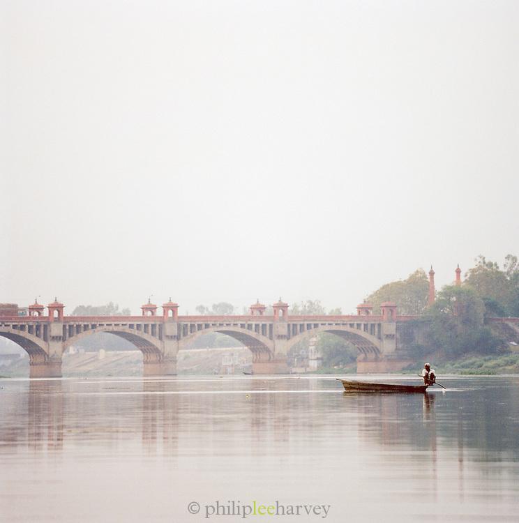 Small boat crossing Gomti River in front of bridge, Lucknow, Uttar Pradesh, India