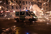 Fireworks explode near a police car in Neukoeln district in Berlin, Germany, 01 January, 2020. The district is well known for wild fireworks activity during new years eve, with people shooting rockets directly at cars and apartment buildings.