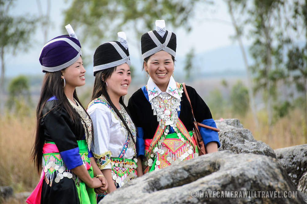Three young Hmong women in traditional costumes for the Hmong New Year pose for a photo amongst the ancient stone jars of the Plain of Jars, Laos.