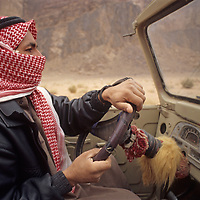 A modern Bedouin drives his vehicle through the sandy terrain of Jordan's Wadi Rum, near the Arabian Desert.
